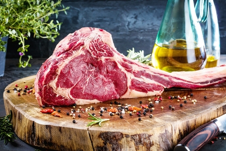 Dry aged raw tomahawk beef steak with ingredients for grilling Banco de Imagens