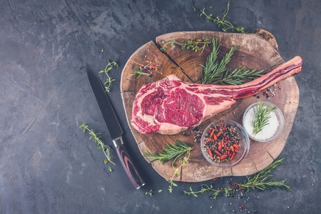 Dry aged raw tomahawk beef steak with ingredients for grilling Stock Photo