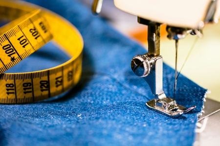 Sewing denim jeans with sewing machine. Repair jeans by sewing machine. Alteration jeans, hemming a pair of jeans, handmade garment industrial concept