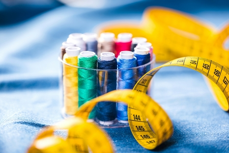 Fabric of various types and objects for sewing. Multicolored fabric, thread reels, needles, a sewing paw are needed for sewing clothes. Banco de Imagens