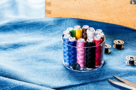 background table top view of sewing tool and jeans on denim fabric.