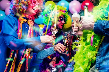 Happy girls and boys at Carnival Party clinking glasses with champagne Stock Photo