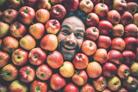 Food industry. Face of laughing man in apple plane. Creative background with apples for your product Stok Fotoğraf