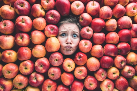 Woman with apples, concept for food industry. Face of laughing woman in apple surface Reklamní fotografie - 118484372