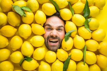 Man with lemons, concept for food industry. Face of emotional man in yellow surface with lemons Stok Fotoğraf