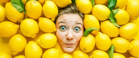 Woman with lemons, concept for food industry. Face of laughing woman in lemon surface Reklamní fotografie - 118484580