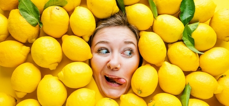 Woman with lemons, concept for food industry. Face of laughing woman in lemon surface Stok Fotoğraf