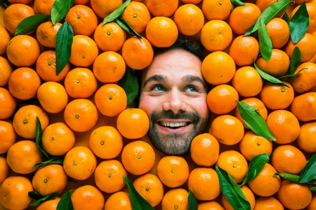 Man with mandarins, concept for food industry. Face of laughing man in tangerines flat.