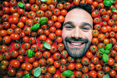 Man with tomatoes, concept for food industry. Face of emotional man in tomato surface