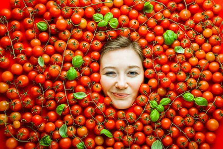 Woman with tomatoes, concept for food industry. Face of laughing woman in tomato surface. Reklamní fotografie