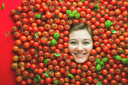 Woman with tomatoes, concept for food industry. Face of laughing woman in tomato surface. Stok Fotoğraf