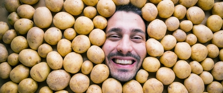 Man with potatoes, concept for food industry. Face of grimacing man in potatoes area Reklamní fotografie - 118484860