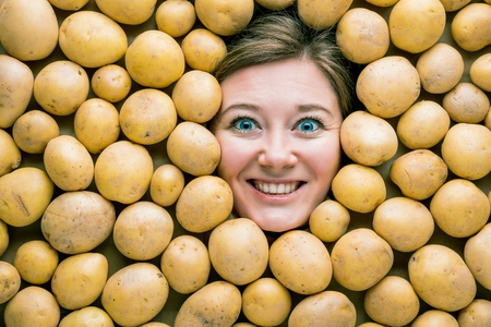 Woman with potatoes, concept for food industry. Face of laughing woman in potato plane Reklamní fotografie - 118484863