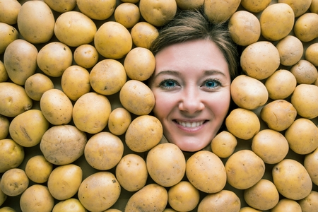 Woman with potatoes, concept for food industry. Face of laughing woman in potato plane