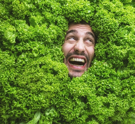 Man with salad leaves, concept for food industry. Face of laughing man in salad area. Reklamní fotografie - 118484888