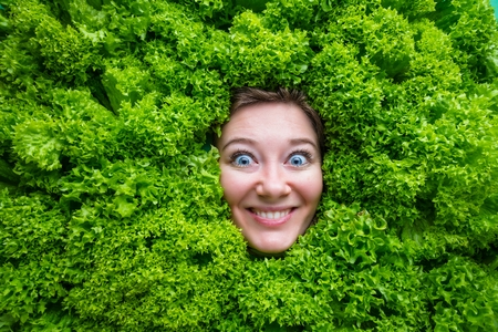 Pretty cheerful young woman posing with fresh green lettuce leaves. Healthy eating concept. Dieting. Reklamní fotografie