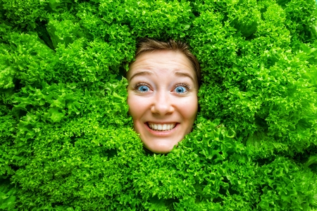 Pretty cheerful young woman posing with fresh green lettuce leaves. Healthy eating concept. Dieting. Stok Fotoğraf