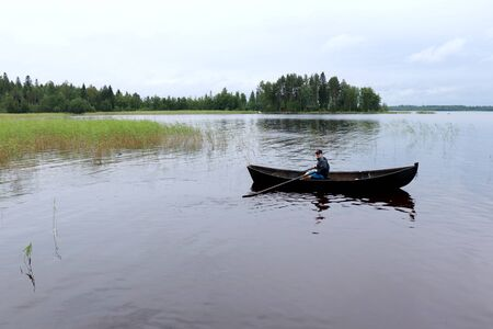 Teenage boy (16) rowing a boat in Lake Saimaa, Finland on a cloudy summer day In july.