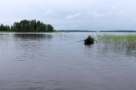 Teenage boy (16) rowing through the weeds on Lake Saimaa, Finland on a cloudy summer day in July with trees in the background. Redactioneel
