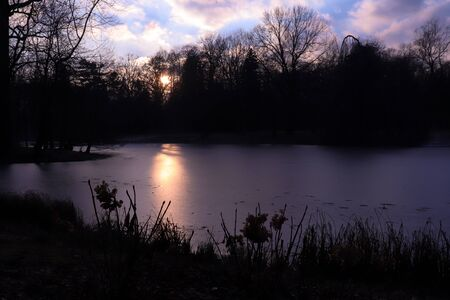 Sun reflecting off frozen lake in Lazienki Park  at sunset on a cold winter afternoon in Warsaw, Poland.