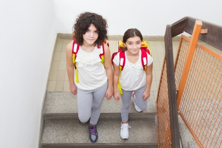 Two sisters go to school  Walking down stairs  Top view photo
