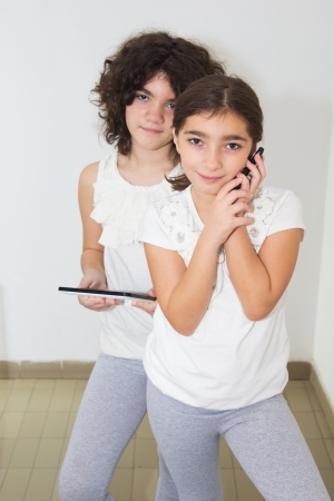 Ten year old twin sisters using computer tablet and smart phone photo