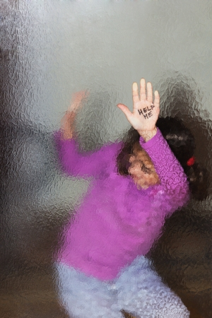 Domestic and family violence  Little girl asking for help  Look through the glass  photo