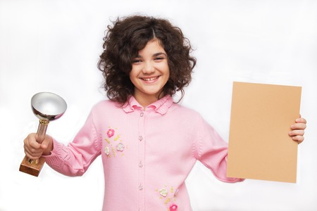 Smiling young girl holding winner cup and diploma  Isolated on white  Banco de Imagens