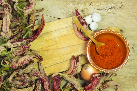 Wooden spoon of cayenne pepper in bowl with cayenne pepper, on wooden table. With paste space. Stock Photo - 25880152