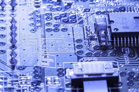 Close up of electronic circuit board with processor. Blue background. photo