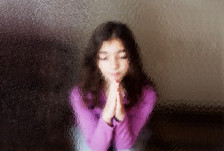 Domestic and family violence. A young girl prays. Look through the glass. photo