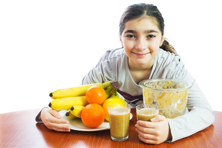 Young girl making fresh fruit juice in her kitchen. White background. photo