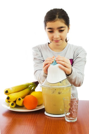 Young girl with mixer making fresh fruit juice in her kitchen. Focus in glass. White background. photo