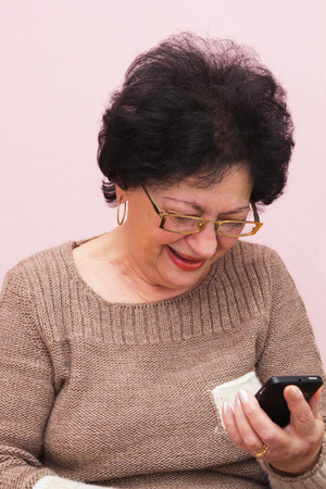 Seventy Year old Woman Using Smart Phone. Light Pink Background. photo