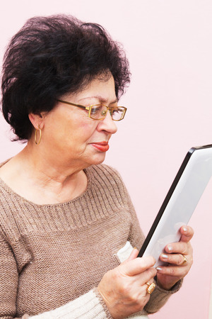 seventy: Settanta anni Donna con tavoletta del computer. Luce Sfondo rosa.