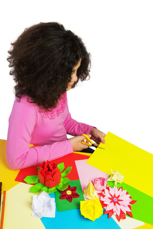 Young Girl Making Decorations with Colorful Paper and Scissors. Isolated on White. photo