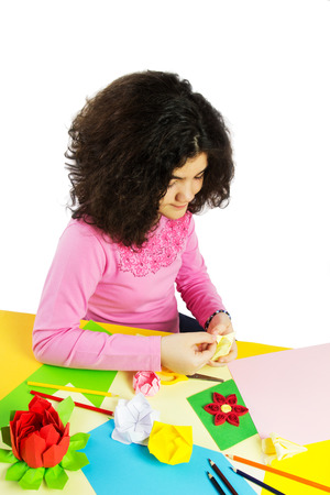 Young Girl Making Decorations with Colorful Paper. Isolated on White. photo