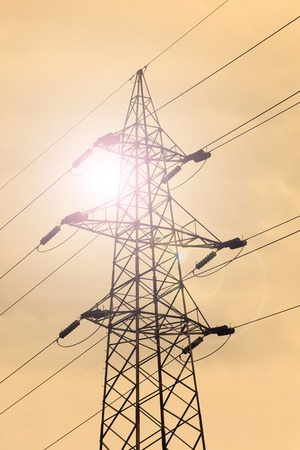 Energy Concept  Electrical Transmission Tower, Sky Background  Sepia Toning  Sun with Lens Flare  photo