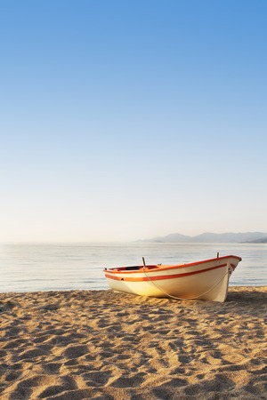 Lonely Boat on the Beach at Sunrise Time. Strimonikos Gulf, Greece. photo