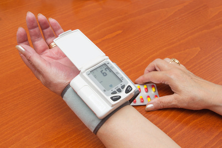 The Hands of an Old Woman Measuring Blood Pressure With a Wrist Meter. photo