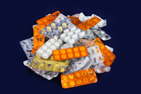 Tablets and Pills in Blister and Many Empty Pill Blister Packages. Isolated on a Blue Background. photo