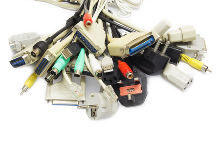 e waste: Old Connecting Cables and Adapters on White .