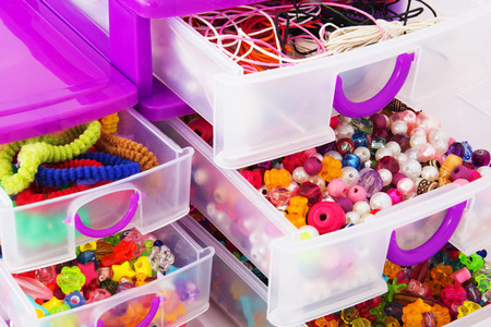 Close-up of Plastic Drawers with Colorful Beads. Isolated on White Background. photo