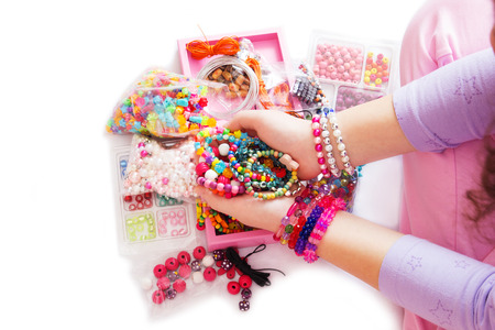 Young Girls Hand with Many Different Beads and Jewelry. Isolated on White Background.