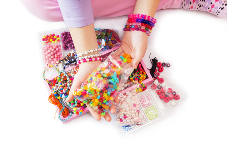 Young Girls Hand with Many Different Beads and Jewelry. Isolated on White Background. photo