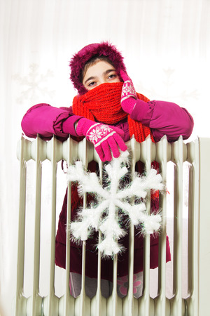 Young Girl in Warm Winter Jacket with Hood Near a Heater. photo