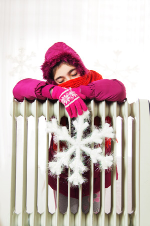 Freezing Young Girl in Winter Jacket Near a Heater. photo