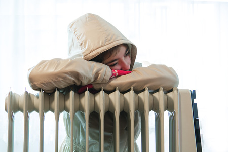 Young Girl in Warm Winter Jacket with Hood Near a Heater. Banco de Imagens