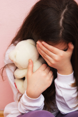 Sad and Lonely Girl Crying with a Hand Covering her Face. photo