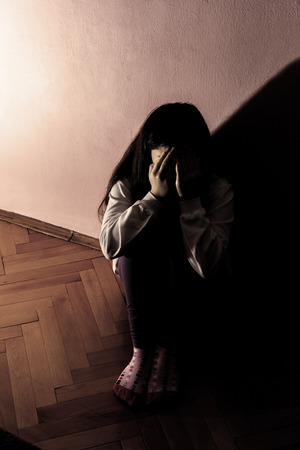 Sad and Lonely Girl Crying with a Hand Covering her Face. Concept: Domestic and Family Violence. Banco de Imagens